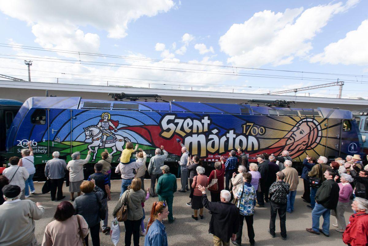 A csíksomlyói búcsúba tartó Székely Gyors és Csíksomlyó Expressz zarándokvonatok a kolozsvári vasútállomáson 2016. május 13-án. A két vonat Budapestrõl egy tizenhat kocsiból álló szerelvényként indult Erdélybe, ahol különválva érik el Csíksomlyót. A csaknem fél kilométer hosszú vonatot Szent Mártont ábrázoló mozdony húzza, és mintegy 1200 zarándok utazik rajta. MTI Fotó: Biró István